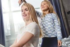 Uśmiechniętej małej córki zgrzywiony włosy jej macierzysty obsiadanie zdjęcie stock