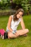Uśmiechniętej nastoletniej dziewczyny siedząca trawa z satchel Zdjęcie Royalty Free