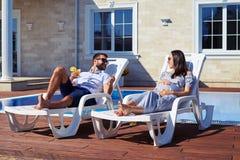 Uśmiechniętej pary relaksujący pobliski basen Obraz Royalty Free