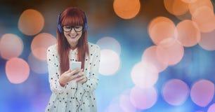 Uśmiechniętej pięknej kobiety słuchająca muzyka przez hełmofonów podczas gdy stojący przeciw defocused światłom fotografia royalty free
