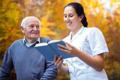 Uśmiechniętej pielęgniarki czytelnicza książka starszy mężczyzna zdjęcia stock