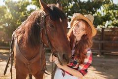 Uśmiechnięty ładny młodej kobiety cowgirl w kapeluszu z jej koniem obraz royalty free