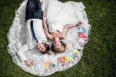 Uśmiechnięty ślub pary lying on the beach na trawie obrazy stock