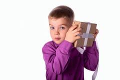 Uśmiechnięty śmieszny dziecko trzyma prezent w jego rękach Zdjęcia Royalty Free