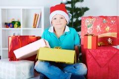 Uśmiechnięty śmieszny dziecko w Santa czerwonym kapeluszu z mnóstwo prezentów pudełkami Obraz Stock