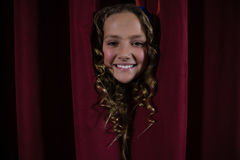 Uśmiechnięty żeński artysty zerkanie przez czerwonej zasłony Fotografia Stock