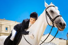 Uśmiechnięty żeński jeździec kocha jej białego konia ogromnie obrazy stock