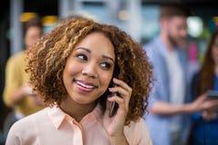 Uśmiechnięty żeński kierownictwo opowiada na telefonie komórkowym zdjęcia royalty free