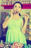 Uśmiechnięty żeński mówienie wiszącą ozdobą i zrywanie cukierkiem Zdjęcie Stock