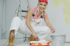 Uśmiechnięty żeński maczanie farby rolownik w tacy obrazy stock