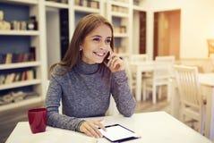 Uśmiechnięty żeński międzynarodowy uczeń opowiada na telefonie Obraz Royalty Free