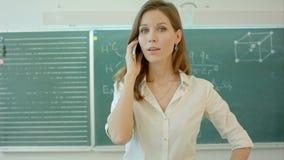 Uśmiechnięty żeński nauczyciel używa smartphone w sala lekcyjnej zdjęcie wideo