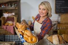 Uśmiechnięty żeński personel trzyma łozinowego kosz różnorodni chleby przy kontuarem Fotografia Royalty Free