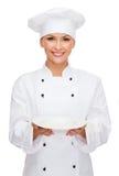 Uśmiechnięty żeński szef kuchni z pustym talerzem zdjęcia stock