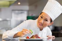 Uśmiechnięty żeński szefa kuchni garnirowania jedzenie w kuchni Zdjęcie Royalty Free