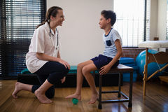 Uśmiechnięty żeński terapeuta klęczenie chłopiec kroczeniem na stres piłce obraz royalty free