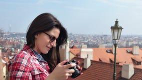 Uśmiechnięty żeński turysta bierze fotografii miasta panoramę używać kamerę cieszy się urlopowego bocznego widok zdjęcie wideo