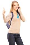 Uśmiechnięty żeński uczeń opowiada na telefonie i daje kciukowi up Fotografia Stock