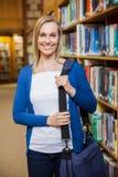 Uśmiechnięty żeński uczeń pozuje w bibliotece Obraz Stock