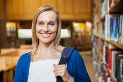 Uśmiechnięty żeński uczeń pozuje w bibliotece Fotografia Royalty Free
