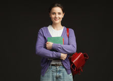 Uśmiechnięty żeński uczeń z książkami i plecakiem Zdjęcie Royalty Free