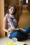 Uśmiechnięty żeński uczeń z książkami w bibliotecznej nawie Obraz Royalty Free