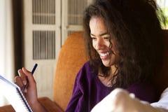 Uśmiechnięty żeńskiego ucznia writing w dzienniczku Obrazy Stock