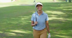 Uśmiechnięty życzliwy kobieta golfisty odprowadzenie na kursie zbiory