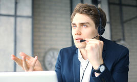 Uśmiechnięty życzliwy przystojny młody męski centrum telefoniczne operator Zdjęcie Stock