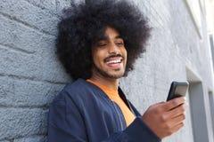 Uśmiechnięty afro mężczyzna używa telefon komórkowego Fotografia Royalty Free