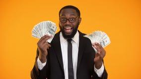 Uśmiechnięty afroamerykański biznesmen pokazuje wiązki dolar gotówka, zysk zbiory