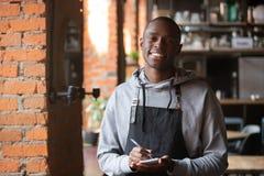 Uśmiechnięty afrykański kelner stoi indoors patrzeć kamerę obraz royalty free