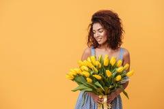 Uśmiechnięty Afrykański kobiety mienia bukiet kwiaty Zdjęcia Stock