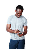 Uśmiechnięty afrykański mężczyzna używa smartphone Zdjęcia Royalty Free