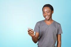 Uśmiechnięty afrykański mężczyzna używa smartphone obrazy royalty free