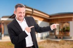 Uśmiechnięty agent nieruchomości wskazuje nowego dom Zdjęcie Stock