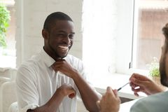 Uśmiechnięty amerykanin afrykańskiego pochodzenia śmia się podczas gdy opowiadający kolega zdjęcie stock