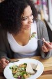 Uśmiechnięty amerykanin afrykańskiego pochodzenia kobiety łasowanie w restauraci Zdjęcia Stock
