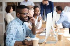 Uśmiechnięty amerykanin afrykańskiego pochodzenia mężczyzna opowiada telefonem, używać komputer fotografia stock