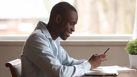 Uśmiechnięty amerykanin afrykańskiego pochodzenia mężczyzny mienia smartphone używać apps texting wiadomość zbiory