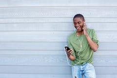 Uśmiechnięty amerykanina afrykańskiego pochodzenia facet słucha muzyka z słuchawkami obrazy stock