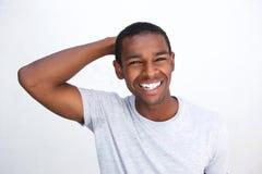 Uśmiechnięty amerykanina afrykańskiego pochodzenia facet z ręką w włosy fotografia stock