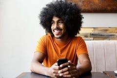 Uśmiechnięty amerykanina afrykańskiego pochodzenia mężczyzna obsiadanie przy stołem z telefonem komórkowym Zdjęcie Royalty Free
