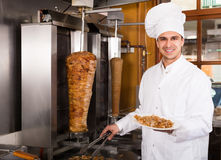 Uśmiechnięty arabski kucharz pozuje blisko mięsa dla kebabu Obrazy Royalty Free