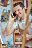 Uśmiechnięty artysta opowiada na telefonie komórkowym w obrazu studiu fotografia royalty free