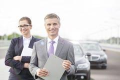 Uśmiechnięty asekuracyjny agent z schowek pozycją przeciw bizneswomanowi awaria samochodem obrazy royalty free