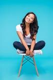 Uśmiechnięty atrakcyjny azjatykci kobiety obsiadanie na krześle zdjęcie stock