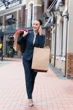 uśmiechnięty atrakcyjny bizneswomanu odprowadzenia formy zakupy i opowiadać Fotografia Stock