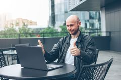 Uśmiechnięty atrakcyjny dorosły pomyślny łysy brodaty mężczyzna w czarnej kurtce z laptopem w ulicznej kawiarni przy miastem fotografia stock
