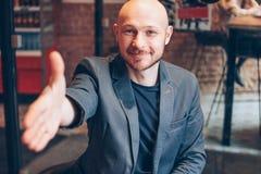 Uśmiechnięty atrakcyjny dorosły pomyślny łysy brodaty mężczyzna w kostiumu z laptopem daje uściskowi dłoni, ręka pomoc, wita przy fotografia stock